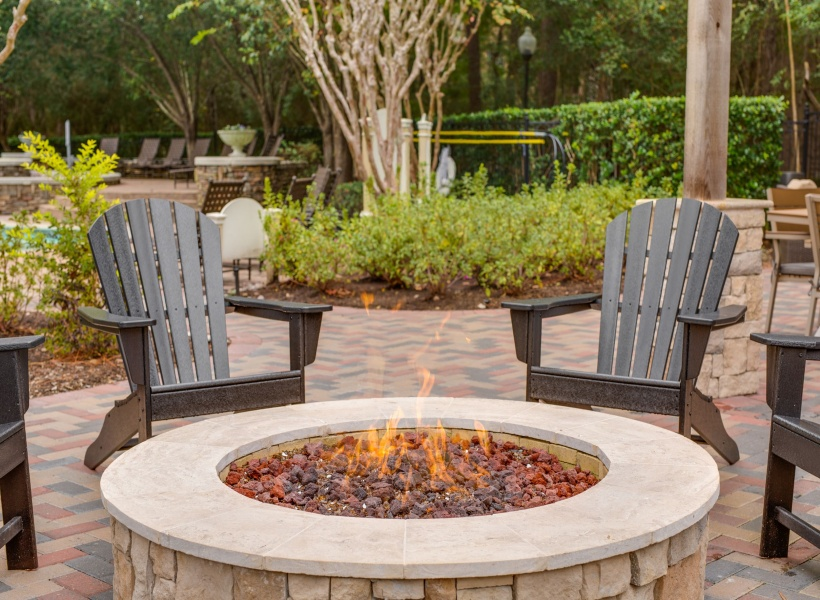 View of Fire Pit Lounge, Showing Outdoor Furniture and View of Pool Area at The Raveneaux Apartments